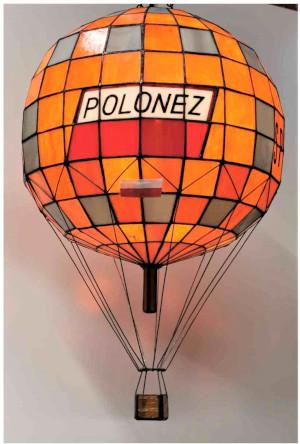 Replika witrażowa balonu SP-B20 Polonez w skali ok. 1:50 na którym Ireneusz Cieślak zdobył w 1983 roku puchar Gordona Bennetta. Replika wykonana przez Sławomira Intka z toruńskiej pracowni witraży. Szklana kula w kształcie balonu w kolorze pomarańczowym stworzona z małych kawałków szkła zlutowanych ołowiem. Napis: Polonez
