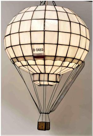 Replika witrażowa balonu D-OWBA Cameron w skali ok. 1:50 na którym Mateusz Rękas i Jacek Bogdański zdobyli w 1983 roku puchar Gordona Bennetta. Replika wykonana przez Sławomira Intka z toruńskiej pracowni witraży. Szklana kula w kształcie balonu w kolorze białym stworzona z małych kawałków szkła zlutowanych ołowiem. Napis: D-OWBA